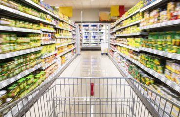 Ein leerer Einkaufswagen zwischen Regalreihen im Supermarkt.