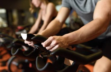 Close-up of hands of a man biking in the gym, exercising legs doing cardio workout cycling bikes. Couple in a spinning class wearing sportswear.